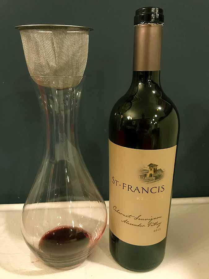 Stainless steel mesh tea strainer sitting on top of wine decanter next to bottle of St. Francis Sonoma County Cabernet Sauvignon Reserve red wine