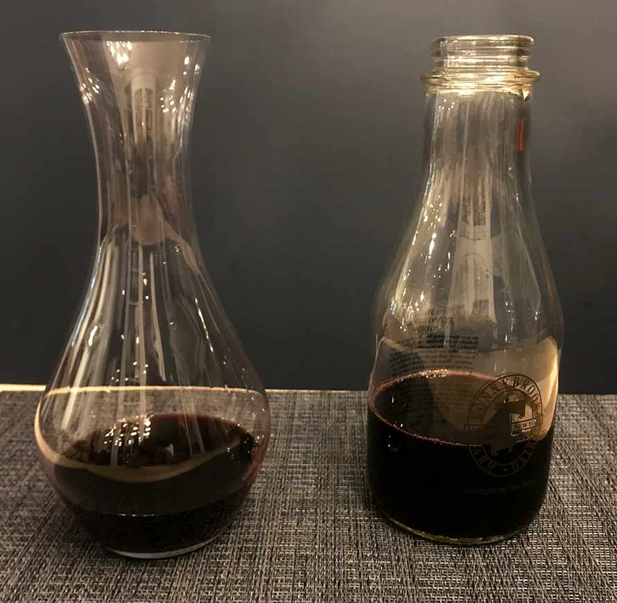 Two vessels used as wine decanters side by side one is a glass milk bottle